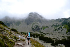 Hiker in the fog. Path and a female hiker in Retezat Mountains, Transylvania Royalty Free Stock Photos