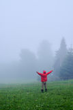 Hiker in fog with outstretched hands. Rear view of man in fog with outstretched hands. Morning in Carpathian mountains Royalty Free Stock Photography