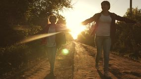 Hiker Girl. children travelers. teen girls travel and hold hands. happy girls travelers with backpacks run along country stock footage