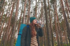 Hiker girl enjoying water. Happy woman tourist with backpack drinking water from bottle in nature. Stock Photography