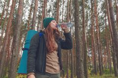 Hiker girl enjoying water. Happy woman tourist with backpack drinking water from bottle in nature. Stock Photos