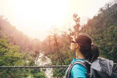 Hiker girl observing mountain from suspension bridge Royalty Free Stock Images