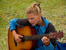 Hiker girl playing guitar. On the hiking camping against the grass background Royalty Free Stock Image