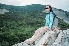 Hiker girl resting on rocks Stock Photography
