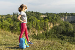 Hiker  girl standing near the cliff looking into the distance. Stock Photography