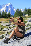 Hiker girl on a stone with mountain walking sticks Stock Photo