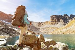 A hiker girl in sunglasses with a backpack and tracking sticks rises to a high rock against the background of rocks and. Slim and sympathetic Girl hiker in royalty free stock images