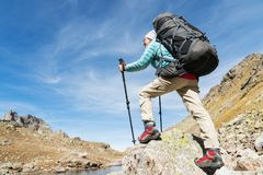 A hiker girl in sunglasses with a backpack and tracking sticks rises to a high rock against the background of rocks and. Slim and sympathetic Girl hiker in royalty free stock photography
