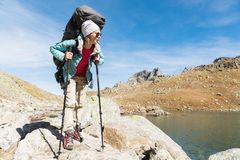 A hiker girl in sunglasses with a backpack and tracking sticks rises to a high rock against the background of rocks and. Slim and sympathetic Girl hiker in stock image