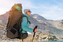 A hiker girl in sunglasses and a hat with a backpack and mountain gear with tracking treks in her hands looks at the Royalty Free Stock Photography