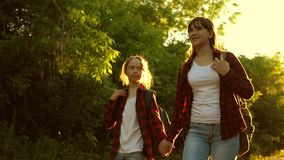 Hiker Girl. teen girls travel and hold hands. children travelers. girls with backpacks are on the country road in the stock video