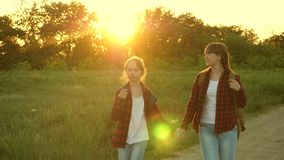 Hiker Girl, teen girls travel and hold hands. children travelers. tourist girls on country road. girls with backpacks stock video