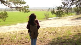 Hiker Girl traveler with a backpack. Woman raise her hands up. Celebrating victory and success in traveling. The tourist. Hiker Girl traveler with backpack stock footage