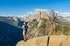 Hiker at the Glacier Point with View to Yosemite Valley and Half Dome in the Yosemite National Park, California, USA stock image