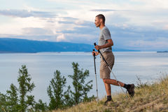 Hiker go down with trekking sticks Stock Photography