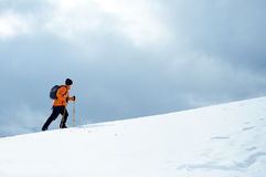 Hiker going up on a slope. Hiker going up on a snow-covered slope Royalty Free Stock Photos