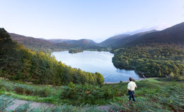 Hiker at Grasmere at dawn in Lake District. Senior man overlooks Grasmere in Lake District as sunrise as sun light mountains Stock Photo