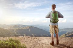 Hiker with a great view. A male hiker with a green backpack is standing on a summit while observing the great view. Tropical mountain view with a low sun level royalty free stock photography