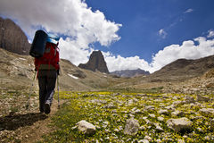 Hiker on green field with big rock in Turkey mountains Royalty Free Stock Photography