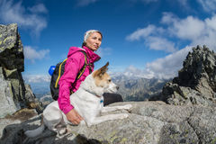 Hiker and her dog on a rocky mountain top Royalty Free Stock Photo