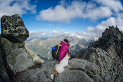 Hiker and her dog on a rocky mountain top Royalty Free Stock Images