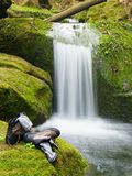 Hiker high boots and sweaty grey socks. Resting on the mossy boulder at the  nice mountain stream Stock Photos