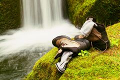 Hiker high boots and sweaty grey socks. Resting on the mossy boulder at the  nice mountain stream Royalty Free Stock Photos