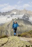 Hiker hikes through a breathtaking alpine landscape in the mountains Royalty Free Stock Photos