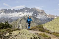 Hiker hikes through a breathtaking alpine landscape in the mountains Stock Image