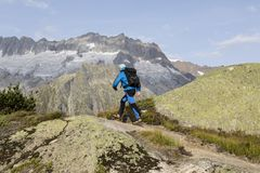 Hiker hikes through a breathtaking alpine landscape in the mountains Royalty Free Stock Image