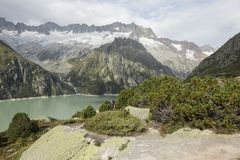 Hiker hikes through the breathtaking mountain scenery in the Alps. Hiker hikes through the breathtaking mountain scenery in the Swiss Alps royalty free stock image