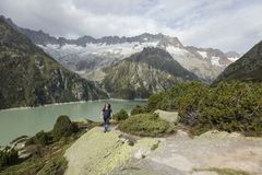 Hiker hikes through a wild high alpine landscape with a lake Stock Photos