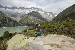 Hiker hikes through a wild high alpine landscape with a lake Royalty Free Stock Image