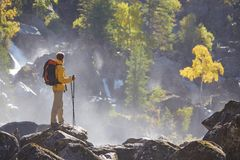 Hiker hiking with backpack looking at mountain river. Hiker hiking with backpack looking at waterfall in park in beautiful summer nature landscape. Portrait of Stock Photos