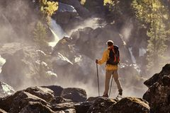 Hiker hiking with backpack looking at waterfall. In park in beautiful summer nature landscape. Portrait of male adult back standing outdoor Royalty Free Stock Image