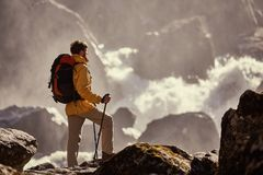Hiker hiking with backpack looking at waterfall. In park in beautiful summer nature landscape. Portrait of male adult back standing outdoor Royalty Free Stock Photography