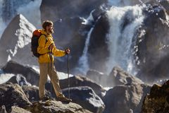 Hiker hiking with backpack looking at waterfall. In park in beautiful summer nature landscape. Portrait of male adult back standing outdoor Royalty Free Stock Photo