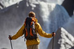 Hiker hiking with backpack looking at waterfall. In park in beautiful summer nature landscape. Portrait of male adult back standing outdoor Stock Photo