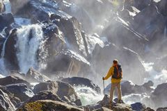 Hiker hiking with backpack looking at waterfall. In park in beautiful summer nature landscape. Portrait of male adult back standing outdoor Stock Image