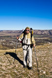 Hiker with hiking poles. Walks in mountains Stock Images