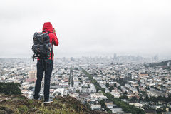 Hiker on hill above city Stock Photo