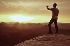 Hiker hold in hand phone and take photo of misty landscape. Stock Image