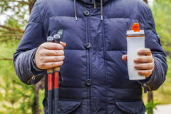 Hiker holding cup with drink and hiking poles Stock Photos