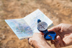 Hiker holding his compass and map in the countryside Royalty Free Stock Photography