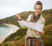 Hiker holding map and pointing in front of ocean view landscape Stock Photography