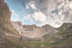 Hiker holding mug and relaxing in alpine valley with lake. Summer adventures and exploration on the Alps. Dramatic sky, toned imag Royalty Free Stock Photo