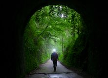 Hiker illuminating the path when entering a tunnel. Hiker illuminating the path when entering a tunnel, Basque Country Royalty Free Stock Image