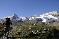 Magnificant mountain region Upper Engadin in the Swiss alps. Hiker on its way up in the magnificant mountain region Oberengadin in the Swiss alps Stock Photo