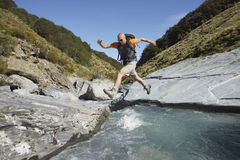 Hiker Jumping Across Forest River. Full length side view of a male hiker jumping across forest river Royalty Free Stock Photos