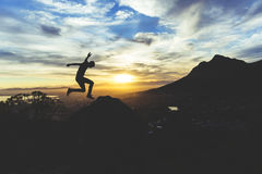 Hiker jumping against setting sun